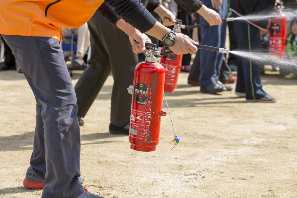 mezczyzni odbywajacy szkolenia bhp uzywaja gasnicy