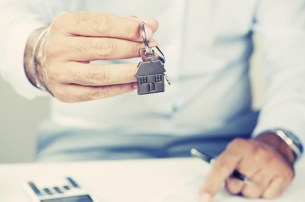 mężczyzna przekazujący klucze z zawieszką w kształcie domu