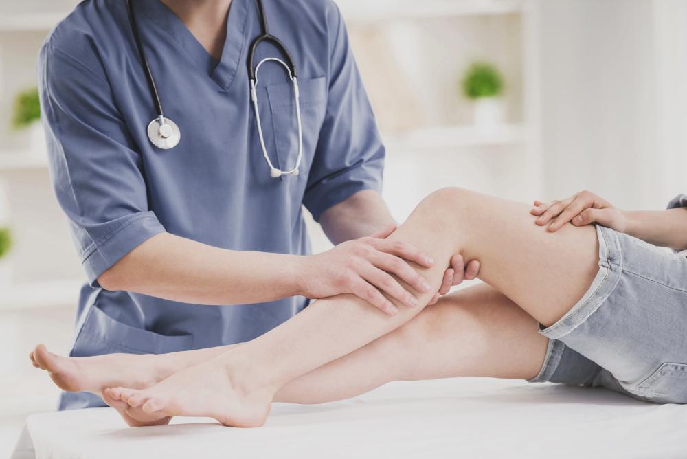 lekarz badający kolano pacjenta