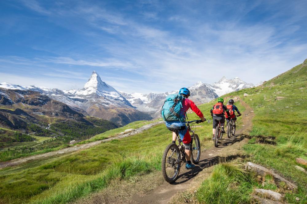 trzy osoby jeżdżące na rowerach po górskich szlakach