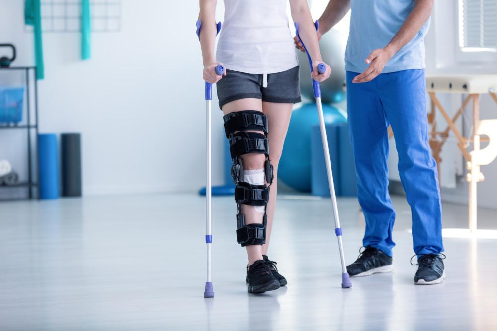 sportowiec u fizjoterapeuty który chodzi o kulach i z usztywniaczem na kolano