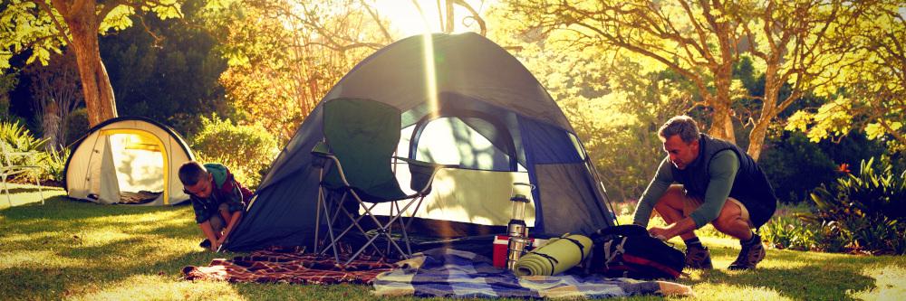 mężczyzna z dzieckiem rozbijający namiot
