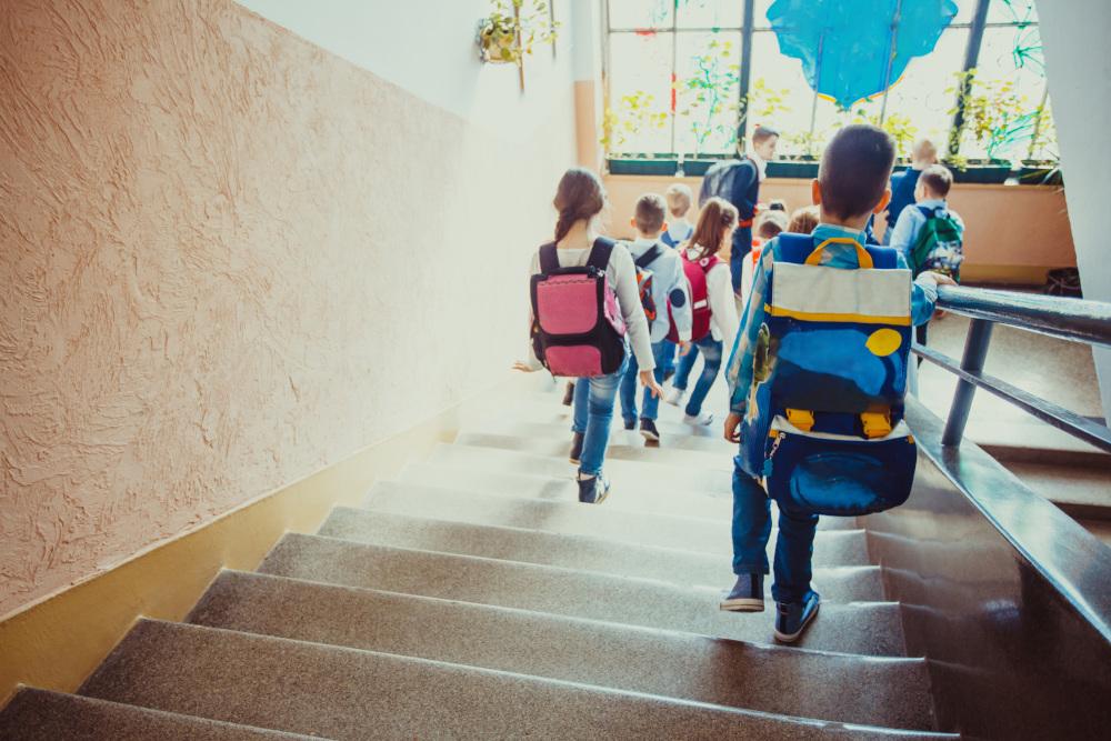 dzieci z tornistrami zbiegające ze schodów w szkole